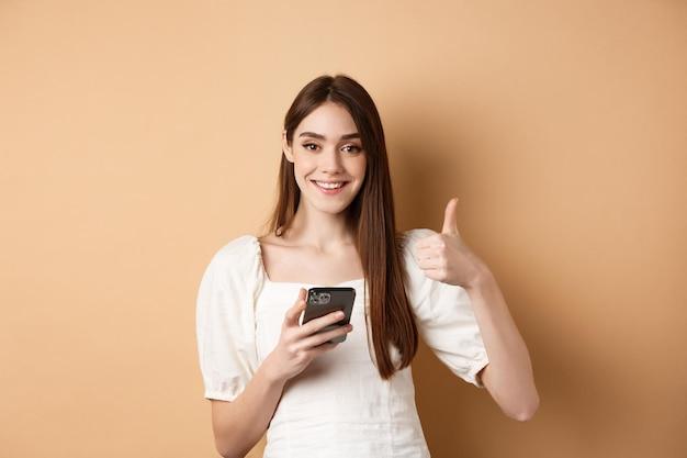 Концепция покупок в интернете. улыбающаяся счастливая женщина показывает палец вверх после использования смартфона, держа телефон и говорит да, стоя на бежевом фоне.