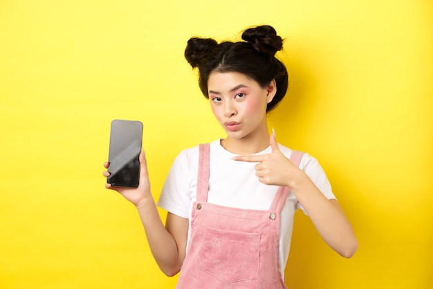 Online shopping concept. stylish asian woman with pink makeup, pointing at empty smartphone sreen, showing good deal, yellow