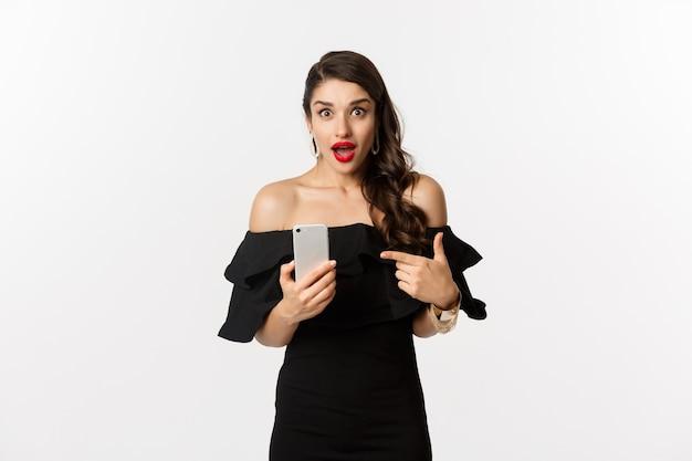 Concetto di acquisto online. elegante donna in abito nero, truccata, puntare il dito al telefono cellulare con emozione sorpresa, in piedi su sfondo bianco.