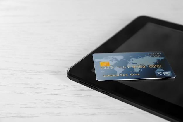 온라인 쇼핑 개념입니다. 나무 배경에 신용 카드가 있는 태블릿