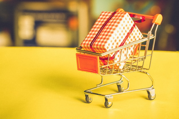 Online shopping concept - trolley cart full of presents.