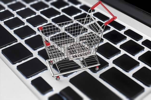 Online shopping concept with 3d rendering shopping cart on keyboard