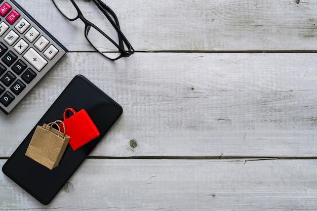 Концепция интернет-покупок с бумажными пакетами для покупок на очках смартфона и калькулятором на белом деревянном столе на виде сверху