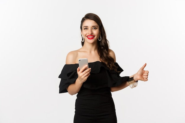 Online shopping concept.  woman in trendy black dress, makeup, showing thumb-up and using mobile phone app, white background.