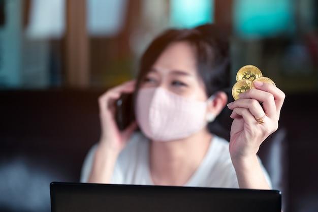 オンラインショッピングのコンセプト、フェイスマスクとビットコインとラップトップコンピューターを自宅で支払いの成功を示す携帯電話を両手で身に着けている女性