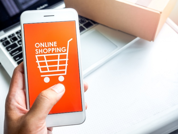 Интернет-магазин концепции. слова «интернет-магазин» и значок корзины покупок на оранжевом фоне на экране смартфона.