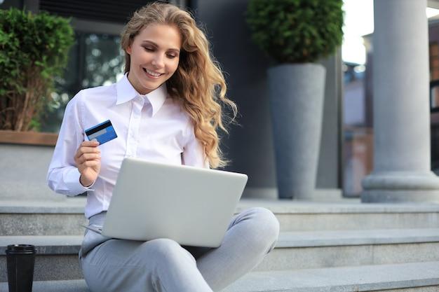 オンラインショッピングのコンセプト。クレジットカードを保持し、屋外のラップトップでオンライン支払いをしている若いブロンドの女性。