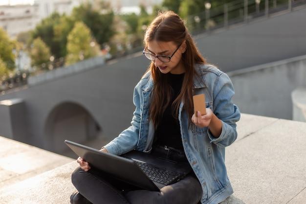 Интернет-магазин концепции. молодая современная женщина в джинсовой куртке и очках держит кредитную карту в руке и онлайн-платежей с ноутбуком на улице в городе