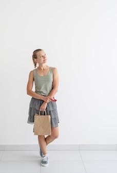 オンラインショッピングのコンセプト。環境にやさしい買い物袋とクレジットカードを持っている若い笑顔の女性