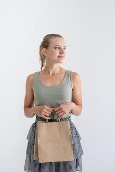 オンラインショッピングのコンセプト。環境にやさしい買い物袋を保持している若い笑顔の女性