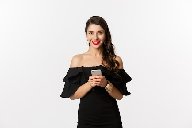 Online shopping concept.  young woman in black dress, reading text message, using mobile phone and smiling, standing over white background.