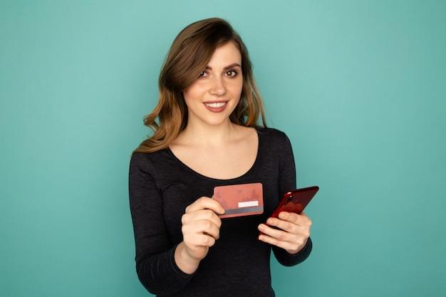 온라인 쇼핑 개념입니다. 신용 카드를 들고 전화로 쇼핑하는 젊은 여자.