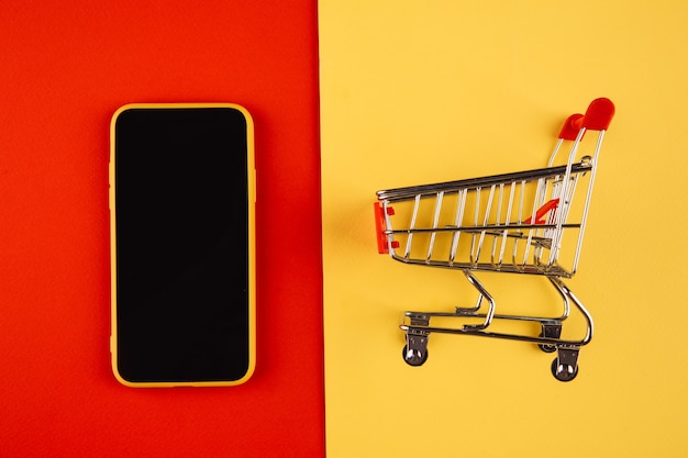 Online shopping concepts with mockup trolley and smartphone on yellow red.