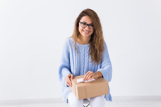 オンラインショッピング、配達、ファッションのコンセプト-家に座っている女性がオンラインの衣料品の購入を行う