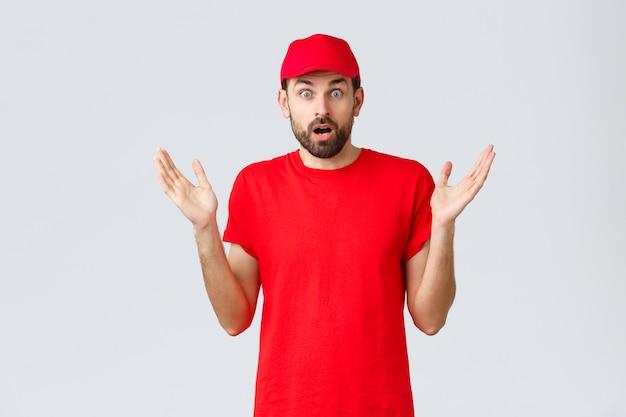 オンラインショッピング、検疫中の配達、持ち帰りのコンセプト。赤いtシャツと会社のサービスのキャップで混乱してショックを受けた宅配便は、優柔不断で神経質に手を上げ、smthを信じることができません