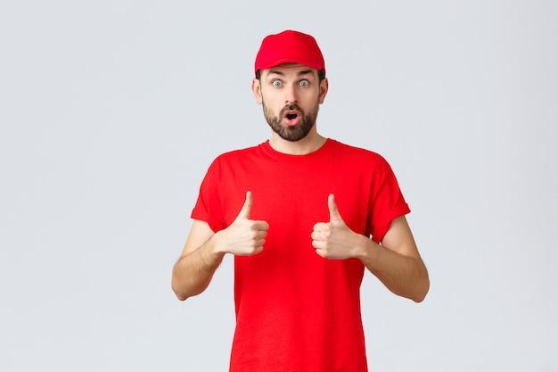 オンラインショッピング、検疫中の配達、持ち帰りのコンセプト。赤いtシャツとキャップのユニフォームを着た感動とショックを受けたひげを生やした宅配便、あえぎながら口を開けて驚いた、親指を立てる、サービスをお勧めします