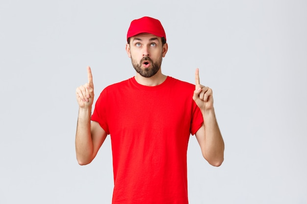 オンラインショッピング、検疫中の配達、持ち帰りのコンセプト。赤い制服の帽子とtシャツを着た、感動した好奇心旺盛な従業員、興味を持って口を開け、バナーを読み、指を上に向ける