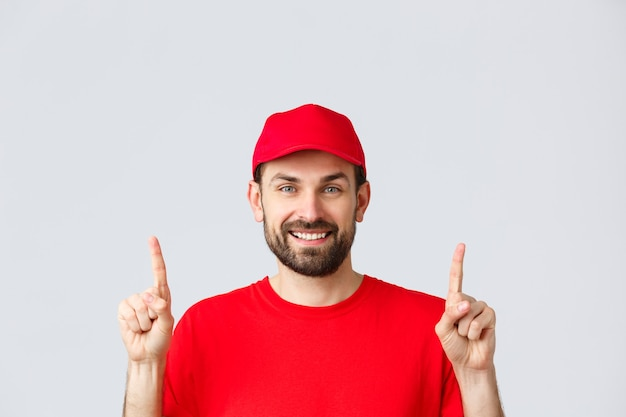 Online shopping, delivery during quarantine and takeaway concept. cheerful bearded smiling courier in red uniform cap and t-shirt, invite take look at promo, pointing fingers up, grey background