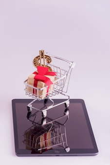 Online shopping and e-commerce concep photo. shopping trolley full of gift boxes on tablet.