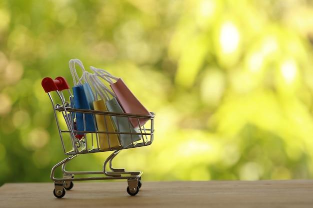 온라인 쇼핑, 전자 상거래 개념 : 트롤리 또는 쇼핑 카트에 종이 쇼핑백. 인터넷에서 제품 구매는 외국에서 상품을 구매할 수 있습니다