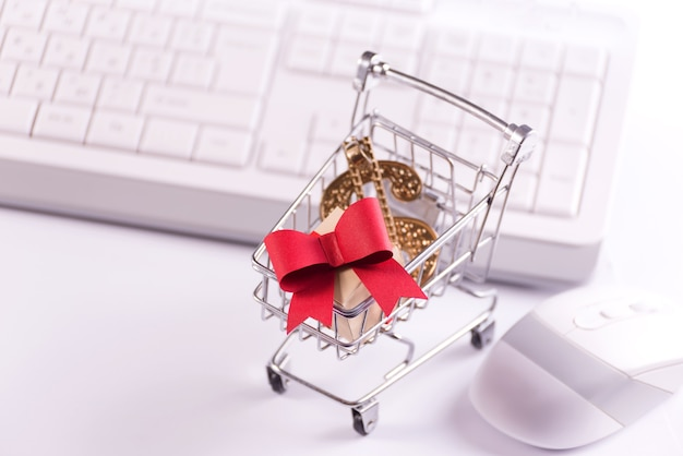 Online shopping and e-commerce concept photo with a shopping trolley full of paper cut gift boxes against the keyboard.