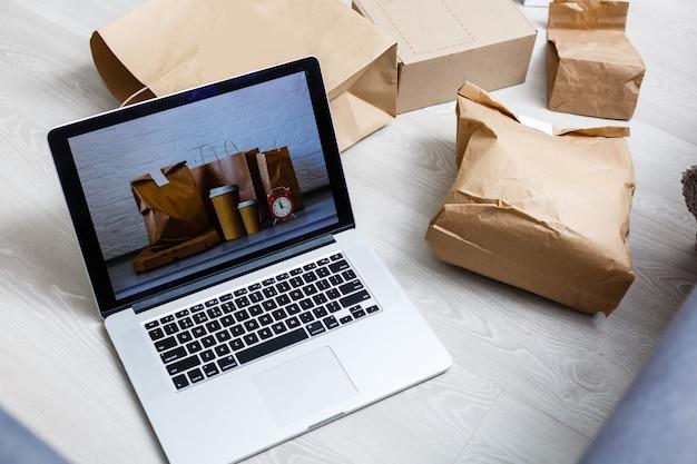 온라인 쇼핑/전자상거래 및 배달 서비스 개념:노트북 키보드에 장바구니 또는 트롤리 로고가 있는 종이 상자는 고객이 인터넷을 통해 소매점 사이트에서 물건을 주문하는 것을 보여줍니다.
