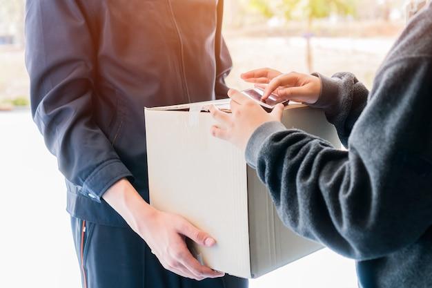 Концепция службы доставки онлайн-покупок / электронной коммерции: пакет доставки на смартфон с подписью азиатского клиента для получения картонных пакетов от почтальона и пункта назначения платежного терминала.
