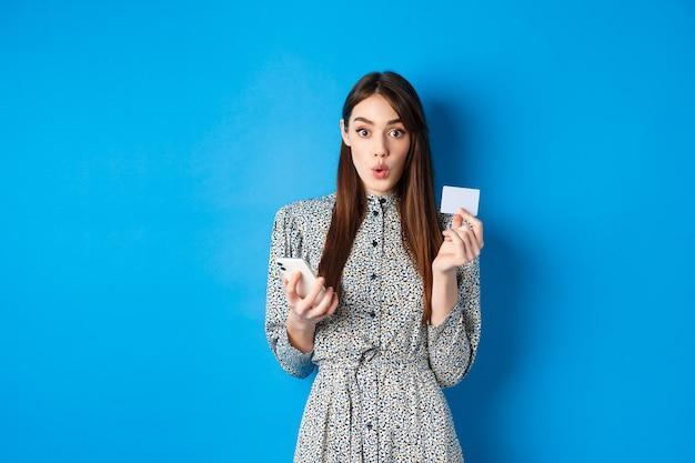 オンラインショッピング。スマートフォンアプリでクレジットカードで支払う興奮した女の子は、青の上に立って、面白がって見えます。
