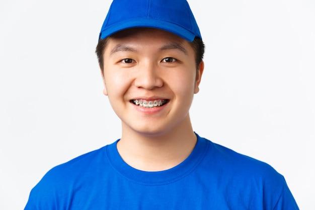 オンラインショッピング、高速配送、従業員、宅配のコンセプト。歯のブレースと笑顔の陽気なアジアの男性の宅配便のクローズアップは、希望と誠実に見え、質の高いサービスを提供します