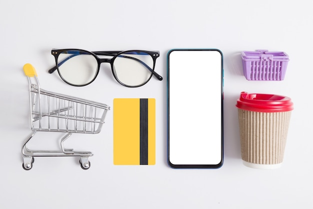 Online shopping flat lay with phone, supermarket trolley, credit card, coffee cup and glasses