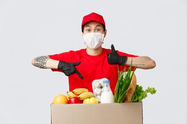 オンラインショッピング、食品配達、コロナウイルスのパンデミックのコンセプト。赤い制服を着たカリスマ的な配達人、医療用マスクと手袋、親指を立てて承認を示し、食料品の小包を指す