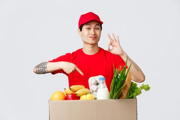 온라인 쇼핑, 음식 배달 및 인터넷 상점 개념. 아웃 클라이언트를 위한 최고의 제품. 빨간 모자와 티셔츠를 입은 택배, 식료품이 포함된 패키지를 가리키는 오케이 사인을 보여주고 품질을 추천합니다.
