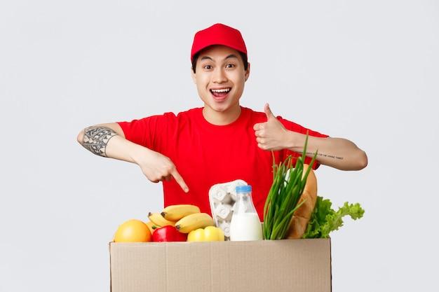 온라인 쇼핑, 음식 배달 및 인터넷 상점 개념. 빨간 티셔츠와 모자를 쓴 웃는 아시아 택배, 엄지손가락을 치켜세워 상품 배달에 대한 양질의 서비스를 추천하고 식료품 패키지 주문을 가리킵니다.