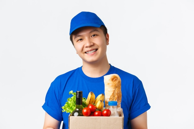オンラインショッピング、食品配達、出荷のコンセプト。笑顔の楽しいアジア人男性宅配便のクローズアップ、青い制服を着て、クライアントに食料品の注文と箱を渡す、白い背景に立っている