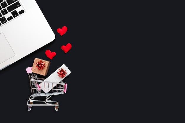 バレンタインデーのオンラインショッピング、ギフトの配達、リモートでのプレゼントの注文。デスクトップ、ボックスと赤いハートのバスケット
