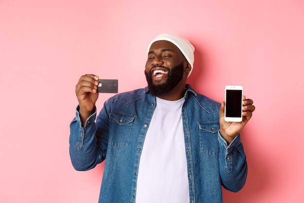 Online shopping. happy african-american man in beanie laughing, showing credit card and mobile phone screen, standing over pink background