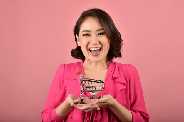 オンラインショッピング、面白いショッピングカートトロリーを保持している幸せなアジアの女性