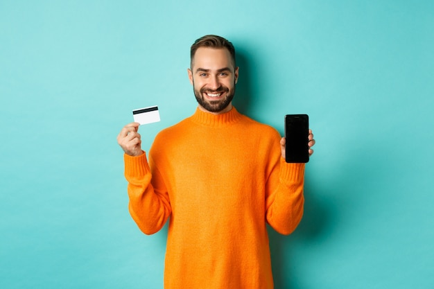 Online shopping. happy attractive guy showing mobile phone screen and credit card, smiling satisfied, standing over light turquoise wall