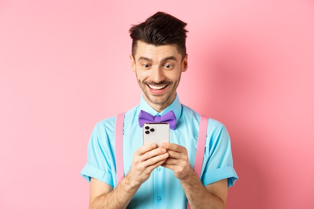 Online shopping happy guy looking at smartphone screen reading message and smiling standing on pink ...