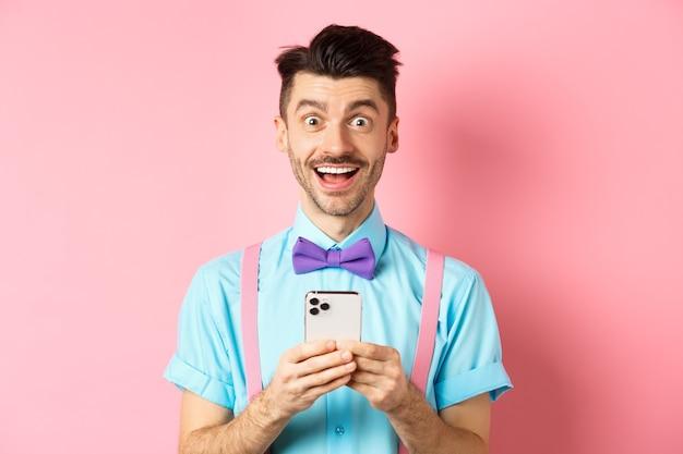 온라인 쇼핑. 스마트 폰 화면을 읽은 후 놀란 찾고 행복 한 사람 분홍색 배경 위에 서 카메라에 흥분 미소.
