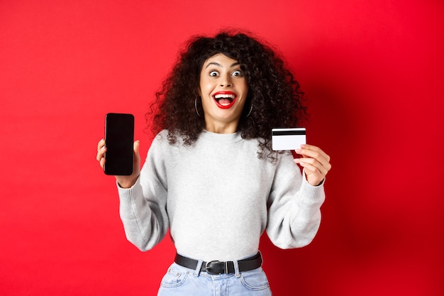 Acquisti online. felice giovane donna che mostra la carta di credito in plastica e lo schermo del telefono vuoto, annuncia l'offerta promozionale, in piedi su sfondo rosso