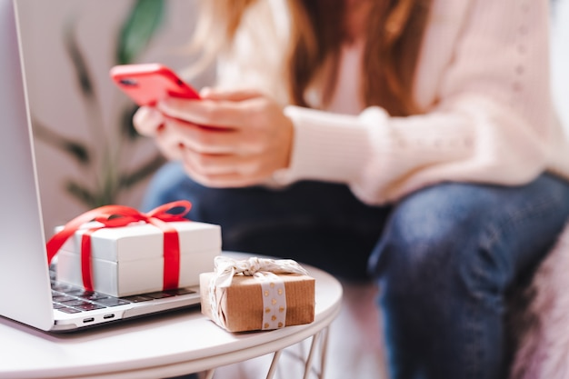 Online shopping at holidays with mobile phone, gifts and laptop