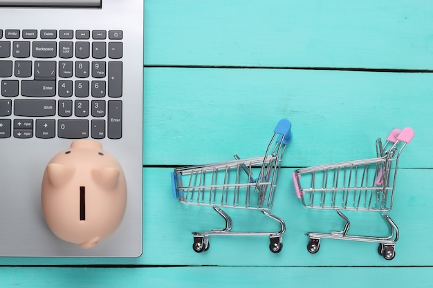 Online shopping ideas. laptop with piggy bank, supermarket trolleys on a blue wooden surface. saving concept. top view
