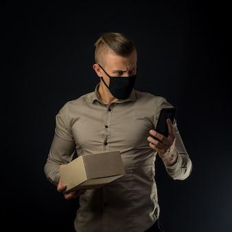コロナウイルスシーズンのオンラインショッピング。黒い壁の上のパッケージを持つ男