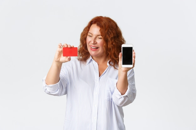 Online shopping, internet banking and money transfer concept. impressed and amused redhead middle-aged woman looking pleased at credit card, showing mobile phone screen, white wall.