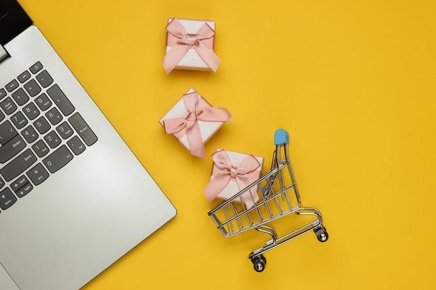 온라인 쇼핑. 노란색 바탕에 활과 노트북 및 선물 상자. 크리스마스, 생일 또는 결혼식을위한 구성. 평면도