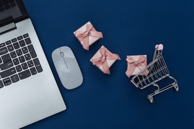 Online shopping. laptop with pc mouse, shopping trolley with gift boxes on classic blue background. color 2020. top view.