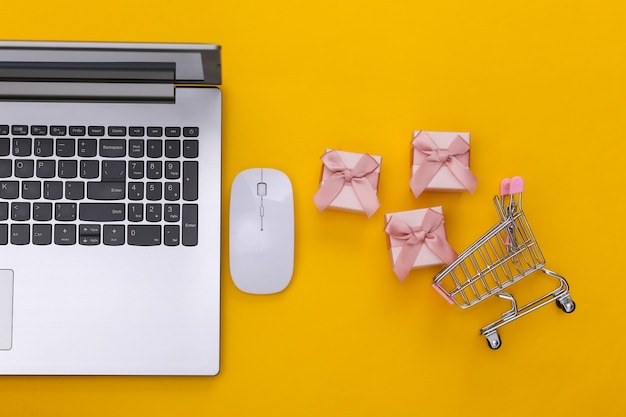Online shopping. laptop with pc mouse, shopping trolley with gift boxes on yellow background. top view.