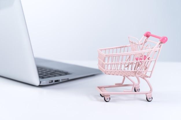 オンラインショッピング。白いテーブルの上のラップトップコンピューター上のミニ空のピンクのショップカートトロリー