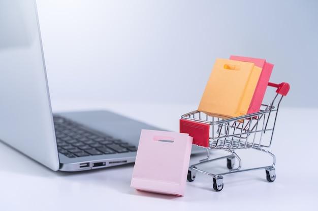 オンラインショッピング。白いテーブルの背景にラップトップコンピューター上のカラフルな紙袋とミニショップカートトロリー、自宅で購入コンセプト、クローズアップ